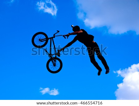 Silhouette image of a cyclist on the background of sky and clouds