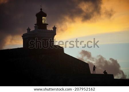 Silhouette image of Castillo San Felipe del Morro, a 16th-century fortress located in San Juan, Puerto Rico, designated as UNESCO World Heritage Site in 1983. - stock photo