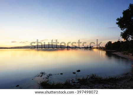 Silhouette image of colorful sky colorful water in lake and mountain before sunrise in the morning:Unfocused image:Ideal use for background.
