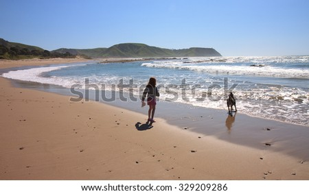 silhouette image of little girl playing with her dog at Pouawa Beach, Gisborne, East Coast, North Island, New Zealand