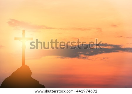 Silhouette Jesus and the cross over sunset on mountain top