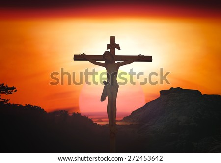 Silhouette Jesus on the cross over blurred sunset background. - stock photo