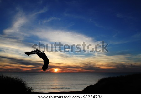 silhouette jumping on beach in sunset - stock photo