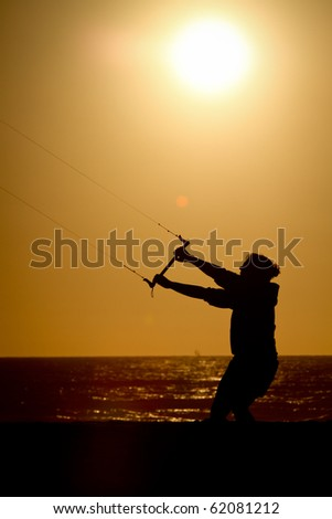 silhouette kite flyer in sunset