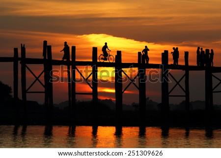 Silhouette life of Ubein Bridge at sunrise, Mandalay, Myanmar - stock photo