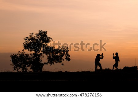 Silhouette man and woman with beautiful the sky at sunset.