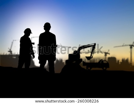 silhouette man engineer looking Loaders and trucks in a building site over Blurred construction worker on construction site - stock photo