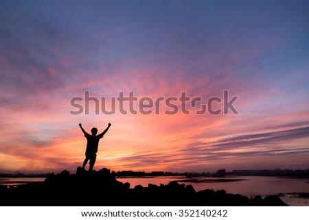 silhouette man Happy celebrating winning success at sunset - stock photo