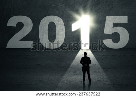 Silhouette man holding briefcase and look at a future door with number 2015 - stock photo
