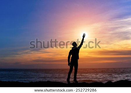 silhouette man holding sun on the sea ocean bank, happy man on beach with hand up on sunset background - stock photo