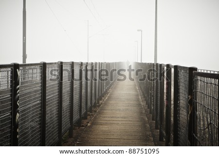 Silhouette man in thick fog on the bridge. - stock photo