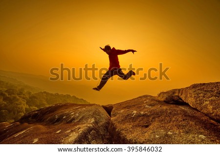 silhouette man jumping into sunset sky
