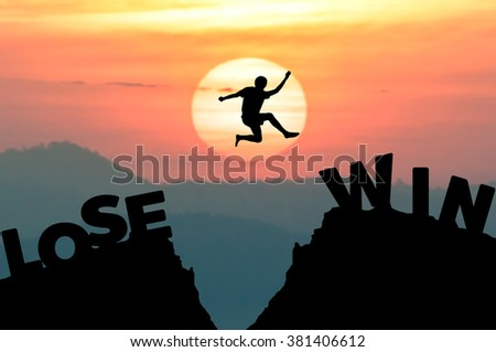 Silhouette man jumps get away from LOSE to the WIN with sunrise. - stock photo