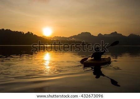Silhouette man kayaking at sunrise - stock photo