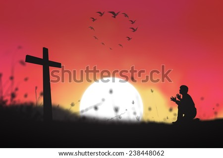 Silhouette man kneeling and raising hands over the cross and birds flying in the shape of heart against beautiful sunset background. - stock photo