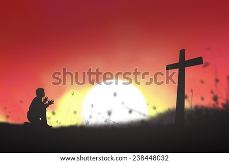 Silhouette man kneeling and raising hands over the cross on a sunset background. - stock photo