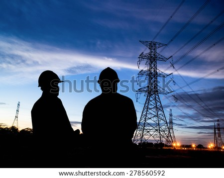 silhouette man of engineers standing at electricity station - stock photo