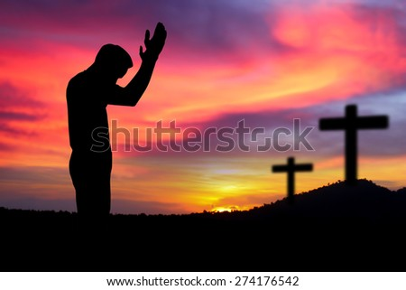 Silhouette man  praying over the cross on beautiful sunset
