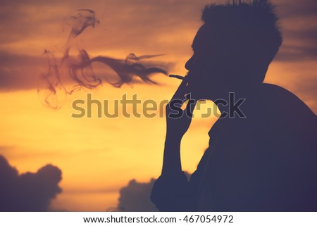 silhouette man smokes a cigarette,World No Tobacco Day.Vintage color