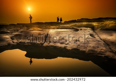silhouette man standing in sunset on cliff  - stock photo