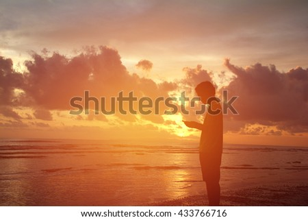 Silhouette man using the phone on the beach. - stock photo