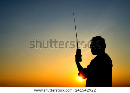 silhouette man with radio communication, sunset on blue sky background - stock photo
