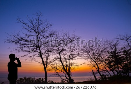 Silhouette man zipping coffee at the beach with dead tree and sunset background - stock photo