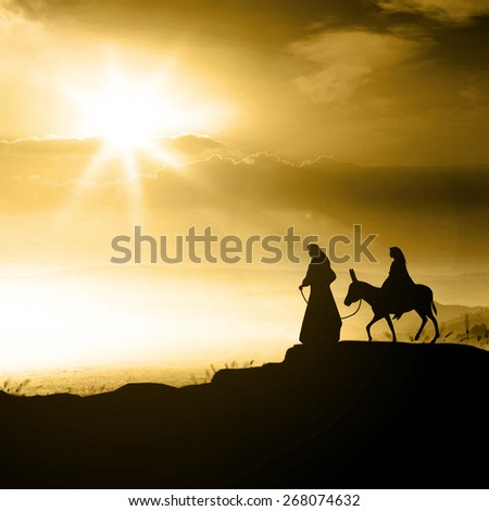 Silhouette Mary and Joseph journeying through the dessert with a donkey on golden light sunset looking for a place to stay on Christmas Eve. - stock photo