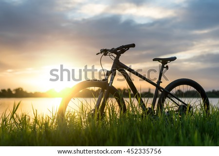 Silhouette Mountain bike sunset at river - stock photo