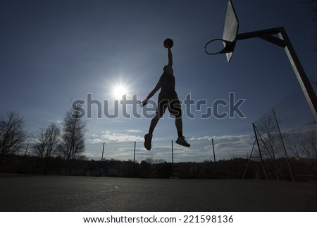 Silhouette of a basketball player in mid air on an outdoor basketball court about to slam dunk on a bright sunny day, motion blur - stock photo