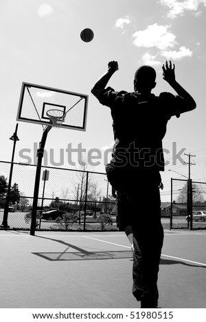 Silhouette of a basketball player shooting the ball at the basket. - stock photo