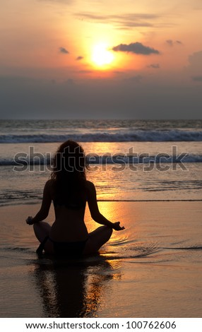 Silhouette of a beatiful woman meditating on a rock by the sea - stock photo