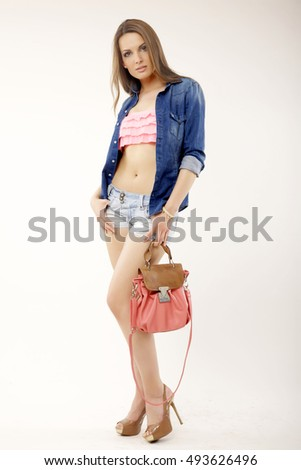 Silhouette of a beautiful and attractive female brunette woman posing in blue jeans short and jacket isolated on white background