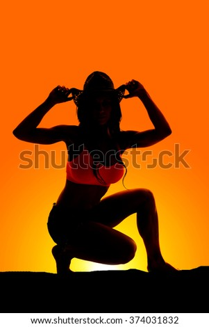 Silhouette of a beautiful cowgirl on one knee. - stock photo