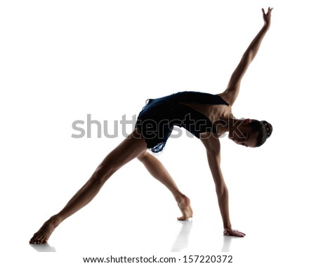 Silhouette of a beautiful female ballet dancer isolated on a white background. Ballerina is barefoot and wearing a dark leotard and short dress. - stock photo
