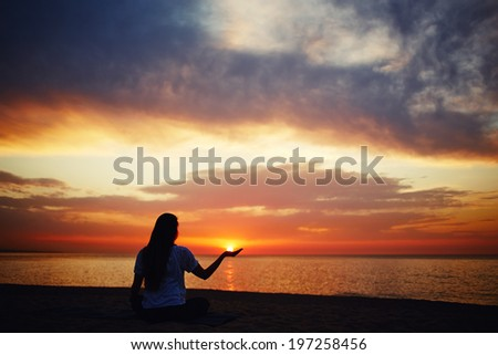 Silhouette of a beautiful girl holding the sun in hand, the morning yoga class