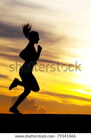 Silhouette of a beautiful running woman against yellow sky with clouds at sunset