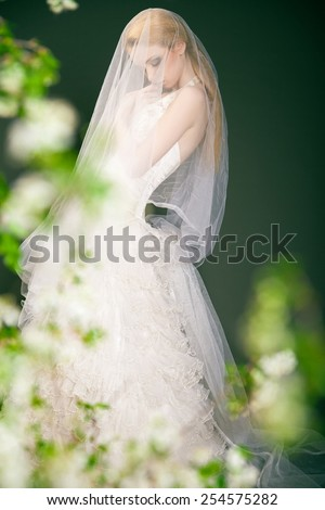 Silhouette of a beautiful thoughtful bride walking somewhere in the park - stock photo