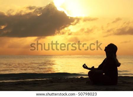 Silhouette of a beautiful woman meditating on the beach by the sea - stock photo
