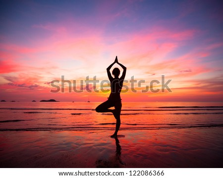 Silhouette of a beautiful yoga woman in the evening on the beach at sunset