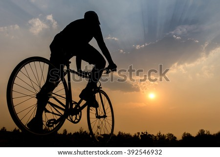 Silhouette of a bike on sky background on sunset - stock photo