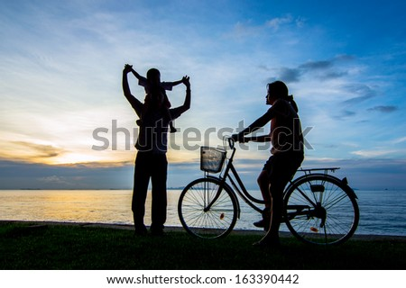 Silhouette of a biker family on the beach at dusk. - stock photo