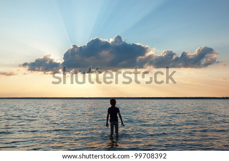 silhouette of a boy at sunset - stock photo