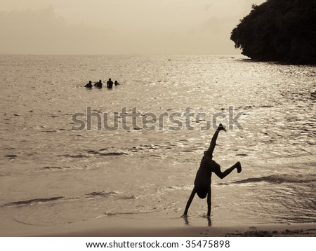 silhouette of a boy doing cartwheels on the beach at sundown - stock photo