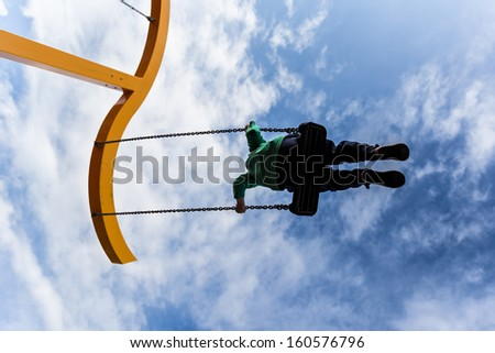 Silhouette of a boy swinging on a swing  against a deep blue sky with puffy clouds - stock photo