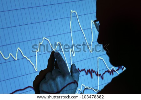 Silhouette of a businessman pointing to a projected graph at a presentation - stock photo