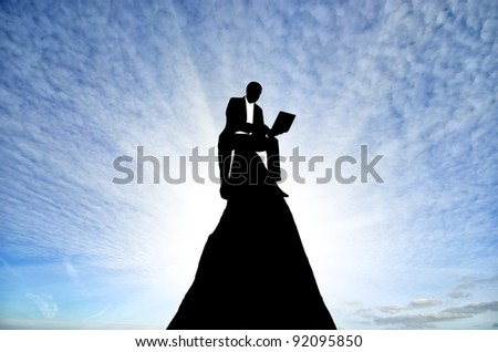 silhouette of a businessman with a laptop in hand is on top of a mountain in the sky with clouds. - stock photo