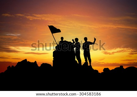 Silhouette of a champion on mountain peak at sunset. - stock photo
