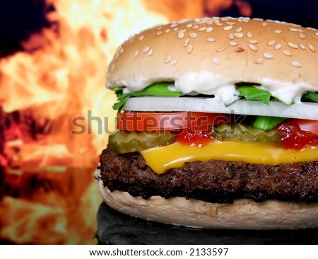 Silhouette of a cheese burger loaded with summer garden vegetables isolated on fire, macro