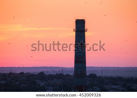 Silhouette of a chimney with flying birds at sunset. Colorful red sky. Industrial landscape - stock photo
